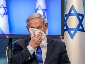 Netanyahu demonstrates how to use a tissue when coughing, during a press conference on March 11, 2020.