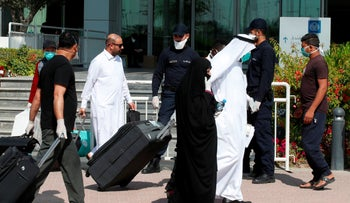 Qatari police stand outside a hotel in Doha as a medical worker walks alongside people wearing protective masks over fears of coronavirus, on March 12, 2020.