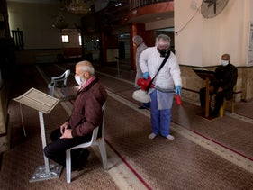 Palestinian workers disinfect a mosque against coronavirus in the West Bank city of Ramallah, Saturday, March 7, 2020.