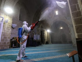 A Palestinian worker disinfects walls inside al-Omari mosque to prevent the spread of the coronavirus, in Gaza City, March 12, 2020.