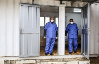 Health workers wearing masks stand at a quarantine zone installed by the Palestinian health ministry in Gaza to test incoming travelers at the Rafah border crossing with Egypt, on February 16, 2020.