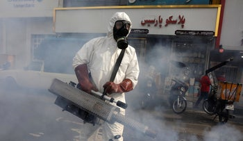 A firefighter disinfects a square against the new coronavirus, in western Tehran, Iran, March 13, 2020.