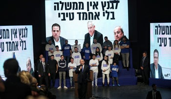 """Netanyahu gives a speech ahead of elections in March in front of screens showing his campaign slogan """"Gantz doesn't have a government without Ahmed Tibi,"""" February 2020."""