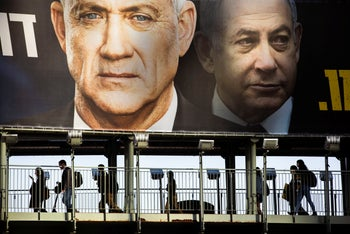 People walk on a bridge under Kahol Lavan election poster, Ramat Gan, February 18, 2020.
