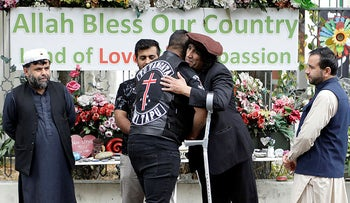 Survivor of the Al Noor mosque shootings, Taj Mohammed Kamran, second from right, welcomes a member of the Tu Tangata motorcycle club to the Al Noor mosque in Christchurch, New Zealand, Sunday, March 15, 2020.