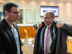 Bank of Israel Governor Amir Yaron, left, with Health Ministry Director General Moshe Bar Siman speak after a coronavirus emergency meeting.