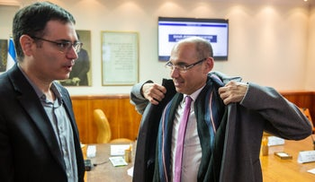 Bank of Israel Governor Amir Yaron, left, withHealth Ministry Director General Moshe Bar Siman speak after a coronavirus emergency meeting.