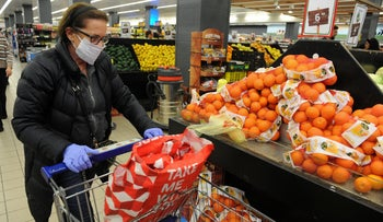 A woman buying groceries at the Stop Market supermarket in Haifa, Israel, March 14, 2020.