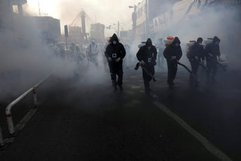 Firefighters disinfect a street against the new coronavirus, in western Tehran, Iran, March 13, 2020.