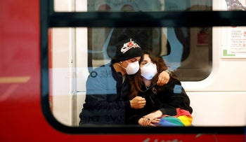 A couple wearing face masks is seen in the subway in Duomo underground station in Milan, as the country is hit by the coronavirus outbreak.