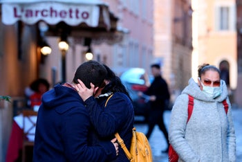 A couple kisses in Rome.