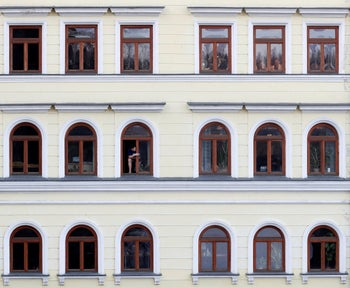 A man looks out of the window near the Charles Bridge in Prague, Czech Republic. The Czech government has imposed further restrictions on the movement in efforts to contain the outbreak of the coronavirus.