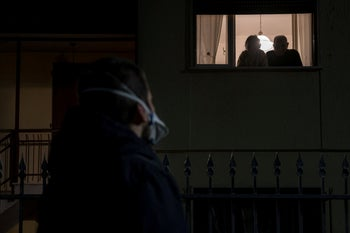A man wearing a mask looks up at a couple looking out of a window from a house on the 15th day of quarantine in San Fiorano, Italy.