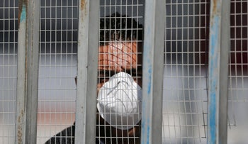 A man looks through a fence as he waits for Palestinians returning from abroad, Rafa border crossing, Gaza Strip, March 8, 2020.