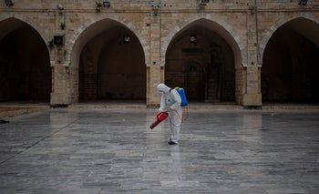 Palestinian Health workers spray disinfectant as a precaution against the coronavirus in the Al-omari Mosque in Gaza City, March 12, 2020.