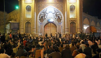 People gather outside the closed doors of the Fatima Masumeh shrine in Iran's holy city of Qom on March 16 2020