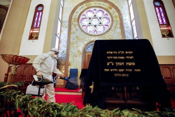 A worker in protective suit disinfects the Neve Shalom Synagogue in Istanbul, Turkey March 16, 2020