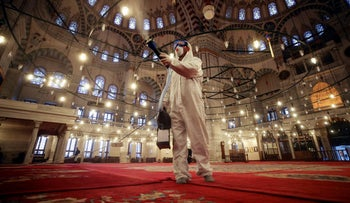 A worker wearing protective clothing disinfects historical Fatih Mosque, in Istanbul, Saturday, March 14, 2020, as a precaution against the coronavirus