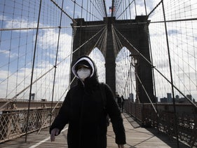A woman wearing a mask as she walks over the normally crowded Brooklyn Bridge, New York