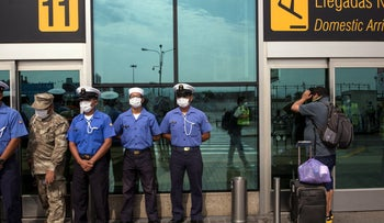 Marines wearing protective masks as a passenger waits to reschedule a cancelled flight at a semi-closed airport, in Lima, Peru, March 17, 2020.