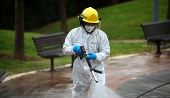 An Israeli firefighter sprays disinfectant as a precaution against the coronavirus in Modi'in, Israel, March 17, 2020.