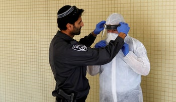 An Israeli police officer helps a Health Ministry inspector put on protective gear up in Hadera, Israel March 16, 2020.