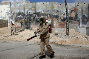 A Palestinian sanitary department worker sprays disinfectant around Aida refugee camp, West Bank, March 16, 2020.