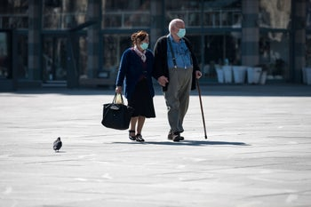 """An elderly couple wearing masks walk through Belgrade's main square, after Serbia's President said new restrictions were necessary to """"save our elderly."""" March 17, 2020"""