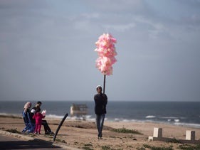 A Palestinian man sells cotton candy on the beach of Gaza City, Saturday, March 7, 2020.