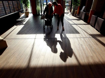 A retirement home employee helps an elderly woman as outside visits are restricted due to coronavirus concerns in Grevenbroich, Germany. March 16, 2020