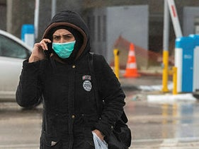 A person walking with a mask, Qalandiya Checkpoint, West Bank, March 18, 2020.