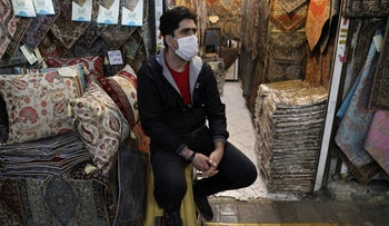 A shopkeeper wearing a face mask to help protect against the new coronavirus, waits for customers at the Tehran's Grand Bazaar, Iran, on March 17, 2020.