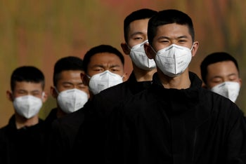 Security personnel wearing face masks to contain the spread of coronavirus disease (COVID-19) walk along a street outside Forbidden City in Beijing, China March 18, 2020.
