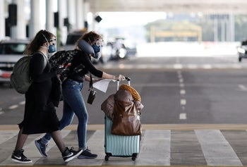 Women wear protective face masks at international arrivals area at Guarulhos International Airport, amid coronavirus fears, in Guarulhos, Sao Paulo state, BraziI March 18, 2020.