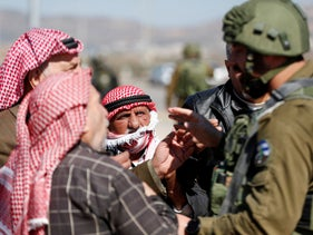 Palestinians argue with an Israeli soldier as Israeli near the village of Qusra, in the West Bank, on March 3, 2020.