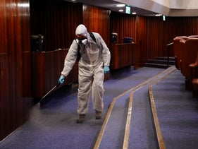 An employee sprays disinfectant at the Knesset, in Jerusalem, Israel, on March 15, 2020.