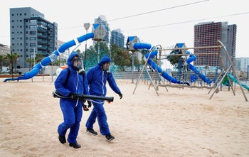 Municipal employees spray disinfectant in a children playground in the Israeli coastal city of Bat Yam on March 18, 2020.