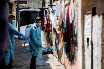 Palestinian volunteers sprays disinfectant a street at al-Shati refugee camp in Gaza City on March 16, 2020.