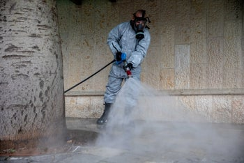 A firefighter disinfecting a sidewalk in Kiryat Ye'arim in the Jerusalem District of Israel, March 18, 2020.