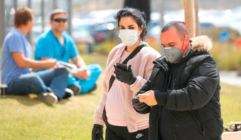 People wearing protective masks walk into Samson Assuta Ashdod University Hospital on March 16, 2020.