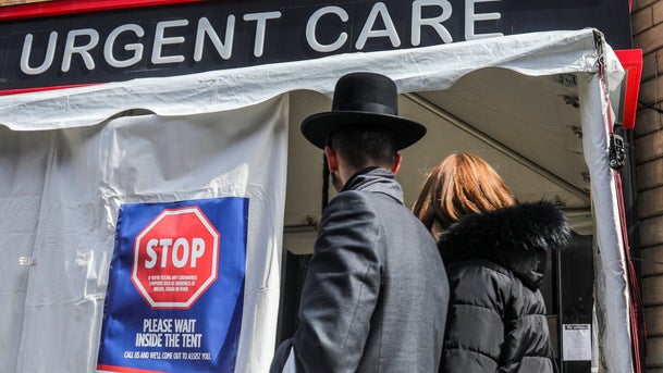 Signs on a tent at the entrance of Chai Urgent Care in Brooklyn's Williamsburg community, asking people who suspect they have the COVID-19 disease to wait inside the tent for screening, March 18, 2020.
