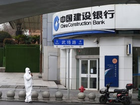A pedestrian in protective suit is seen neat a branch of China Construction Bank in Wuhan, the epicentre of the novel coronavirus outbreak, Hubei province, China February 26, 2020.