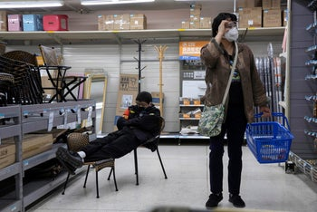 A shopper wearing a mask walks past a security guard napping in a supermarket in Beijing.