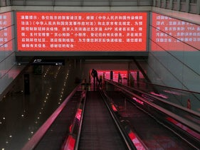 A worker mops the area under a screening showing China's regulations related to the coronavirus outbreak at the Capital International Airport terminal 3 in Beijing.