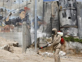 A Palestinian sanitation worker sprays disinfectant against coronavirus infection around the Aida refugee camp near Bethlehem, with Israel's separation barrier in the background. March 16, 2020