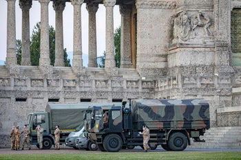 Italian military trucks are seen by Bergamo's cemetery after the army was deployed to move coffins to neighboring provinces amid the coronavirus outbreak, in Bergamo, Italy, March 18, 2020