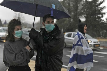 People wearing protective masks against coronavirus during a protest outside the Knesset (parliament) in Jerusalem on March 19, 2020.