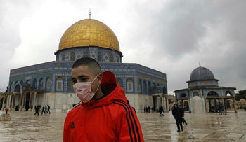 A young man wearing a protective mask for protection against the coronavirus in front of the Dome of the Rock mosque inside the al-Aqsa compound in the Old City of Jerusalem, March 6, 2020.