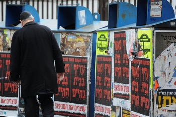 A religious man walks past signs urging people to stay home at the Talpiot market in Haifa, March 19, 2020.