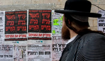 An ultra-Orthodox man walks past signs urging people to stay home at the Mea She'arim neighborhood in Jerusalem, March 18, 2020.